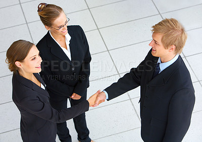 Buy stock photo Cropped shot of two business colleagues shaking hands while a third looks on