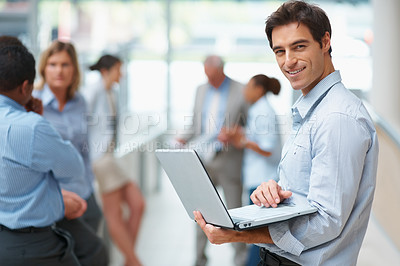 Buy stock photo Portrait of a smart business man using a laptop while standing in a corridor, with colleagues in the background