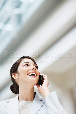 Buy stock photo Young pretty executive using cellphone while looking upwards at copyspace
