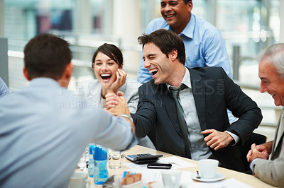 Buy stock photo Laughing business colleagues at a business meeting , two colleagues joining hands in unity