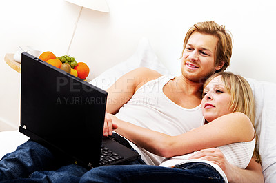 Buy stock photo Young couple browsing the internet from their own bed.