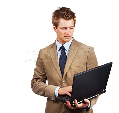Buy stock photo A young businessman standing up using a laptop
