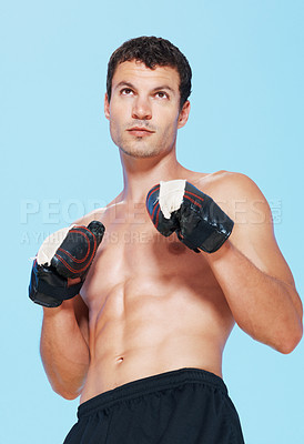 Buy stock photo Portrait of young handsome man ready to punch on blue background
