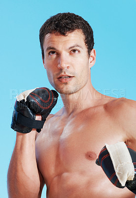 Buy stock photo Portrait of young powerful man ready to punch on blue background