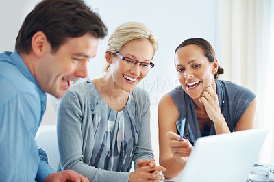 Buy stock photo Portrait of cheerful business people having a positive discussion in front of a laptop in the office