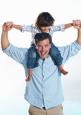 Buy stock photo Portrait of cute little son enjoying ride on father's shoulder against clear sky