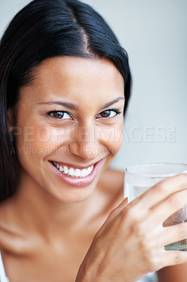 Buy stock photo Closeup of smiling mixed race woman holding glass of water