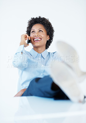 Buy stock photo African American female executive using cellphone with legs on desk