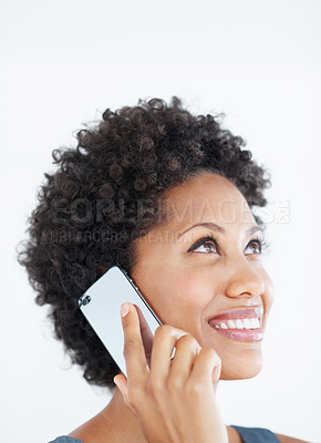 Buy stock photo Closeup of smiling African American woman speaking on mobile phone while looking up over white background
