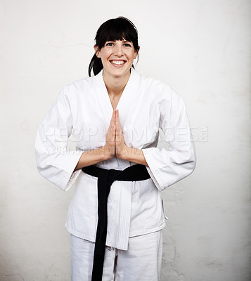 Buy stock photo Studio portrait of a young woman bowing in her karate gi