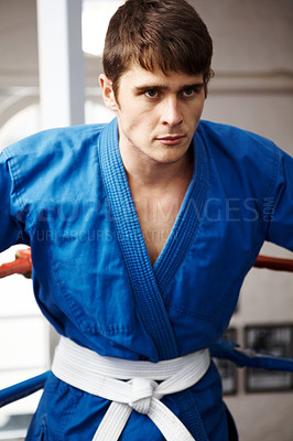 Buy stock photo Cropped shot of a serious young martial artist looking focused in the ring