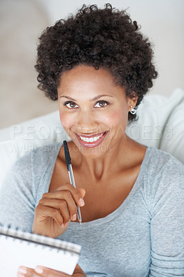 Buy stock photo Portrait of smiling African American woman writing in notepad at home