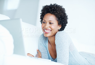 Buy stock photo Low angle view of charming African American woman using laptop while lying on couch