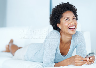 Buy stock photo Beautiful woman in sofa laughing while reading text message on mobile phone