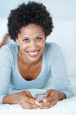 Buy stock photo Portrait of lovely African American woman smiling while reading text message on couch