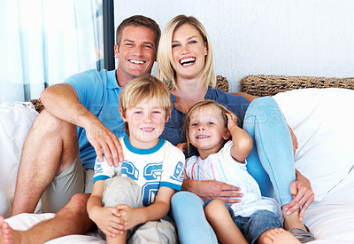 Buy stock photo Portrait of beautiful happy couple relaxing on sofa with cute children