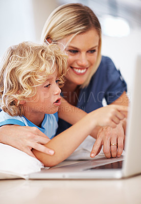 Buy stock photo Closeup of beautiful happy woman using laptop with little son pointing at screen
