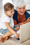 Woman using laptop with granddaughter
