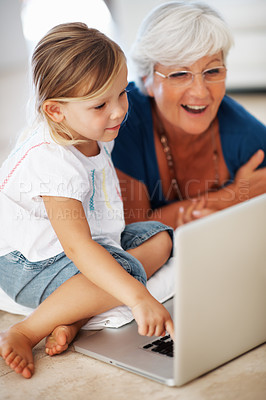 Buy stock photo Adorable little girl using laptop with grandmother at home