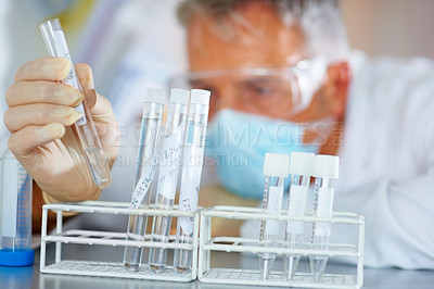 Buy stock photo Male scientist conducting a experiment using a test tube
