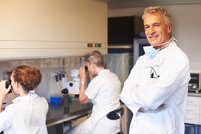 Buy stock photo Successful scientist with two female assistants working in background on microscope