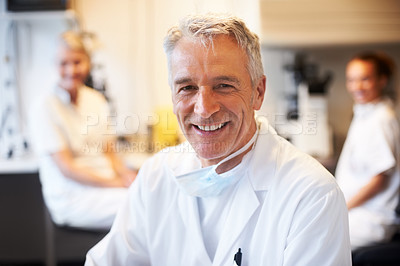 Buy stock photo Happy mature scientist with colleagues in background at the laboratory