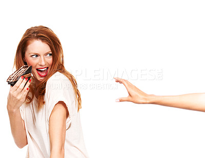 Buy stock photo A young woman holding her piece of cake away from a grabbing hand