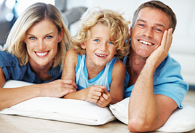 Buy stock photo Portrait of cute little boy lying on floor with parents and smiling