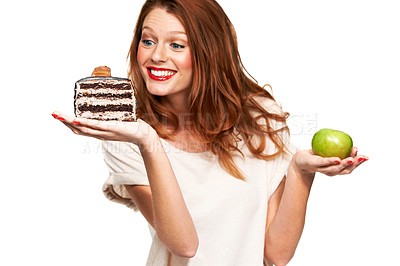 Buy stock photo A young woman choosing a piece of cake over a healthy apple