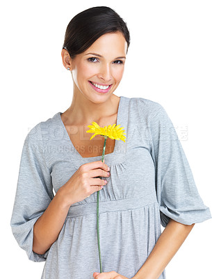 Buy stock photo Gorgeous brunette holding a yellow gerber daisy while smiling sweetly at the camera
