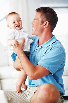 Buy stock photo Happy middle aged man smiling playing with cute baby at home