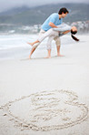 Love symbol on beach with a romantic couple in background