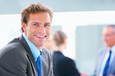 Buy stock photo Business executive smiling with his colleagues in the background