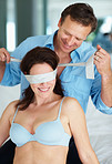 Smiling man blindfolding his wife in bed