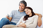Mature couple watching television on white background