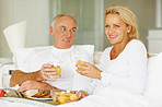 Smiling mature couple eating breakfast in bed