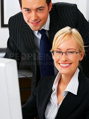 Buy stock photo Two business colleagues sitting by a screen at a desk in their office.