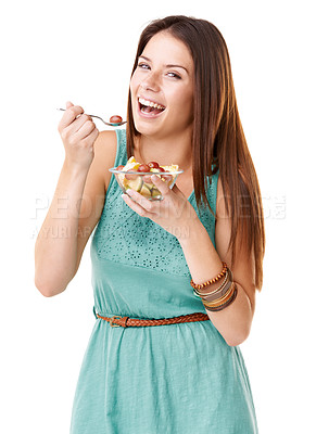 Buy stock photo Studio portrait of an attractive young woman eating a bowl of fruit salad isolated on white