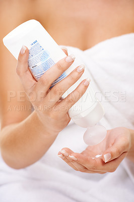 Buy stock photo Cropped shot of a young woman squeezing body lotion onto her hand