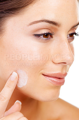 Buy stock photo Cropped image of a young woman applying lotion to her face