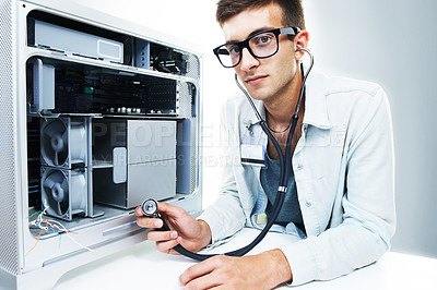 Buy stock photo Studio portrait of a young man working on a computer hard drive