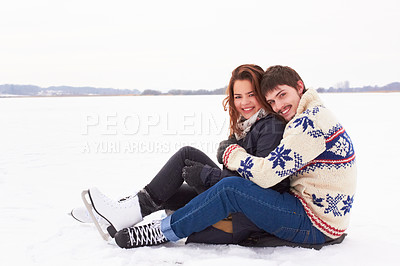 Buy stock photo Sweet young couple in ice skates cuddling on the ice of a frozen natural lake outdoors