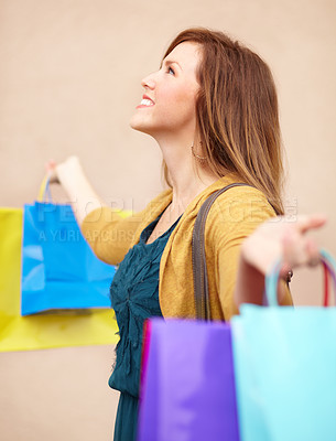 Buy stock photo Cropped shot of an attractive young woman with shopping bags looking upwards