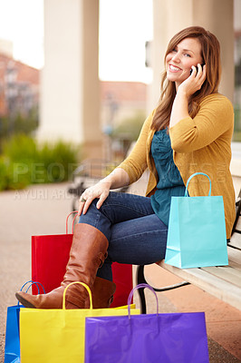 Buy stock photo Shot of a beautiful woman talking on her cellphone while surrounded by shopping bags