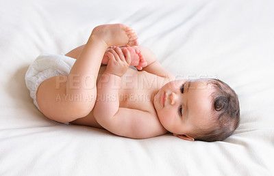 Buy stock photo High angle shot of a cute baby lying on a bed