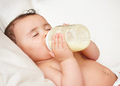 Buy stock photo Close up shot of a baby drinking from a bottle with her eyes closed