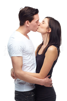 Buy stock photo A happy young couple hugging and kissing each other while isolated on white