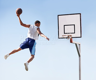 Buy stock photo A sportsplayer makes a flying slam dunk