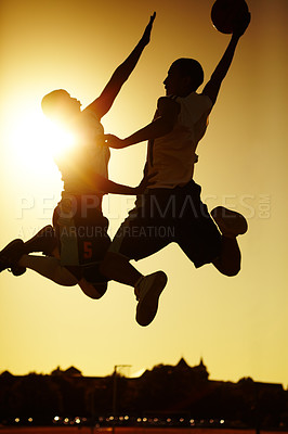 Buy stock photo Two basketball players playing at sunset