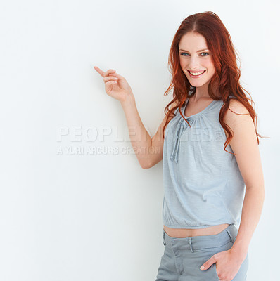Buy stock photo An attractive woman pointing at copyspace
